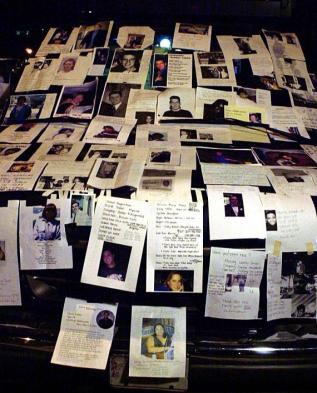 NEW YORK, UNITED STATES: Photographs of missing people from the 11 September 2001 World Trade Center attack sit on a television truck outside Bellevue Hospital in New York 12 September, 2001 where family members and friends stand vigil in hopes of getting information from authorities and help from media exposure. AFP PHOTO/JOHN MOTTERN (Photo credit should read JOHN MOTTERN/AFP/Getty Images)