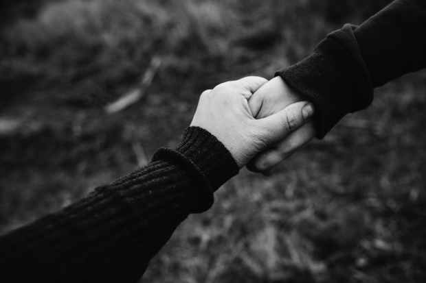 black and white photo of holding hands
