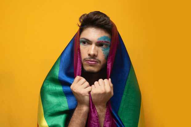 man holding rainbow color flag