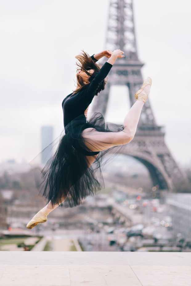 ballet dancer performing stunt with eiffel tower background