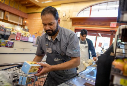 A Gelson's cashier rings up a customer.