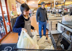 Alejandra Ortez loads bags into a cart for a customer at Gelson's Market in Santa Barbara.