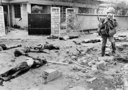 South Vietnamese soldier walks among bodies of dead Viet Cong guerrillas killed during street fighting in suburbs of Saigon during mini Tea Offensive of Vietnam War in 1968
