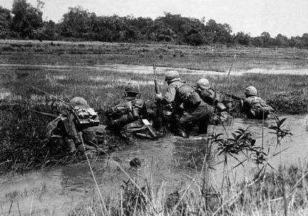 American army combat platoon leader Second Lieutenant John Libs (center) of 2nd platoon, C Company, 2d Battalion, 16th Infantry Regiment, 1st Division, surveys the situation with his men from the relative safety of a watery rice paddy as they prepare to advance on a Viet Cong sniper position, Vietnam, mid 1960s. Libs and the rest of 2nd Platoon participated in the battle of Xa Cam My/Operation Abilene in April 1966 during which Charlie Company suffered 82% casualties. (Photo by Hulton Archive/Getty Images)